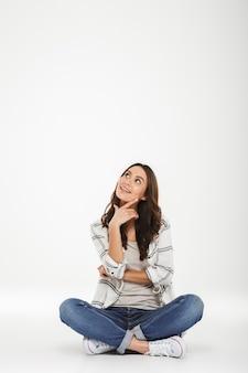 ロータスで座っているカジュアルな服装でブルネットの女性の全身画像は、白い壁に分離された上向きの顔と率直な笑顔で床にポーズします。