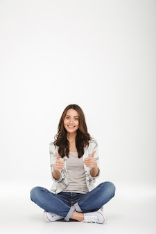ジーンズとスニーカーで足を組んで座っているフルレングスの笑顔の女性は、白い壁に分離された床ジェスチャー親指を渡った