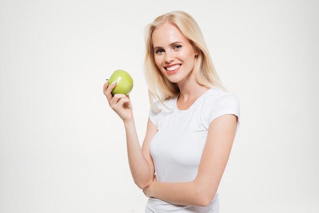 Портрет счастливой женщины, держащей зеленое яблоко