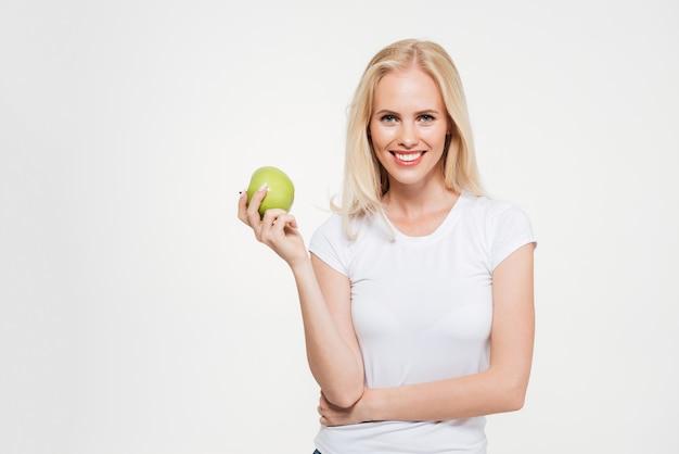 Портрет молодой здоровой женщины, держащей зеленое яблоко
