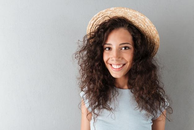 帽子で幸せな巻き毛の女性