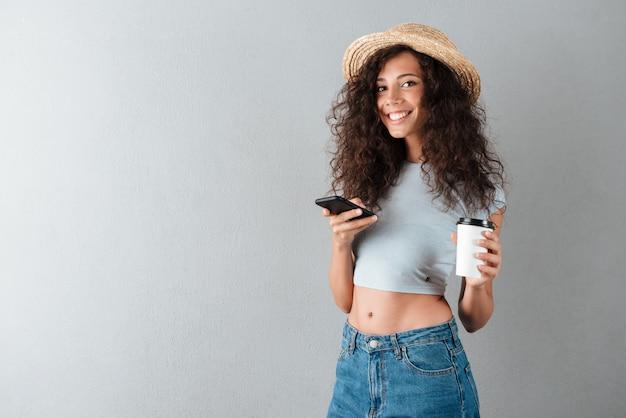 Молодая женщина с кофе в чате на смартфоне