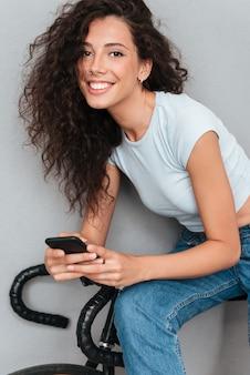スマートフォンを使用して、自転車に座っている巻き毛を笑顔