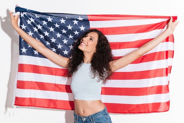 Молодая женщина, держащая американский флаг, изолированные