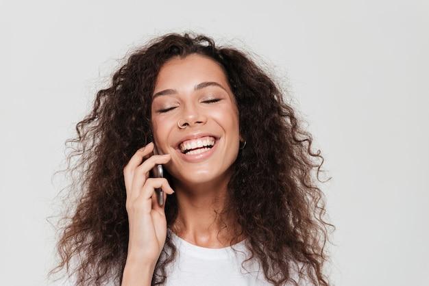 Смеющаяся кудрявая женщина, которая разговаривает по смартфону
