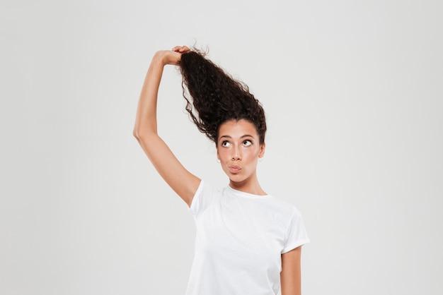 Красота кудрявой женщины, подтягивая ее волосы