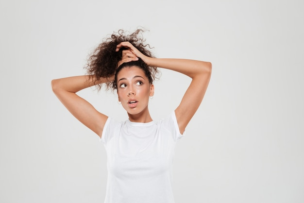 Красота кудрявой женщины связывает волосы в студии