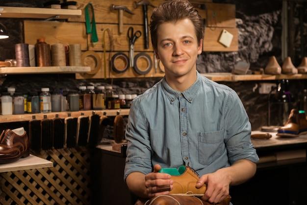 Веселый сапожник в мастерской держит обувь