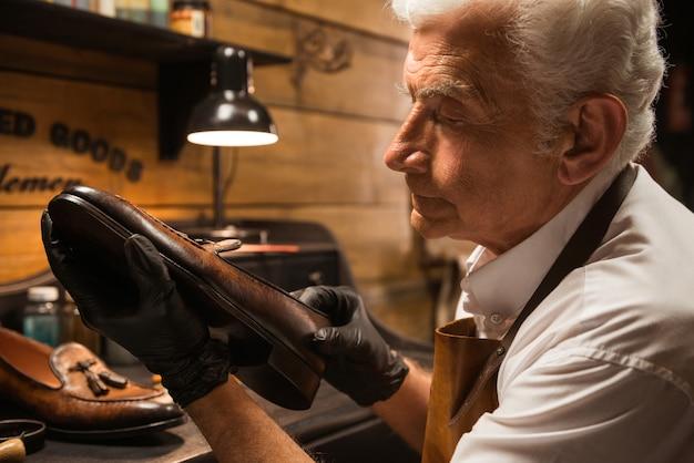 Концентрированный сапожник в мастерской по изготовлению обуви