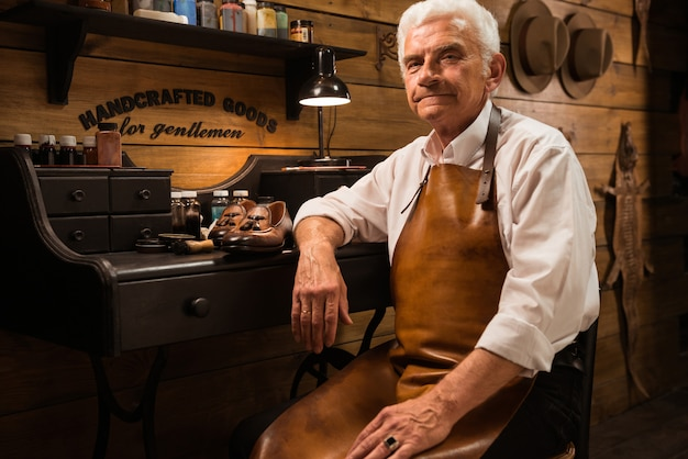 Зрелый улыбающийся сапожник в мастерской