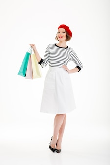 Полная длина счастливая рыжая женщина с рукой на бедре и пакетами позирует, глядя в камеру на сером