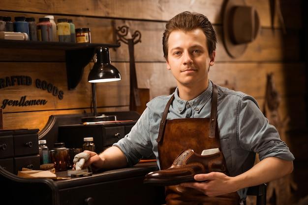Сапожник в мастерской держит обувь