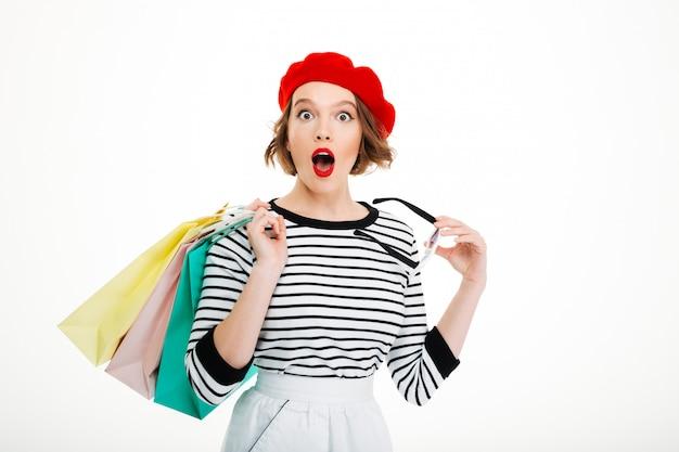 Потрясенная рыжая женщина с пакетами смотрит в камеру над серым