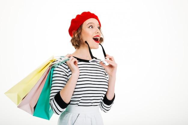 Удивленный рыжий женщина с пакетами и солнцезащитные очки, глядя на серый
