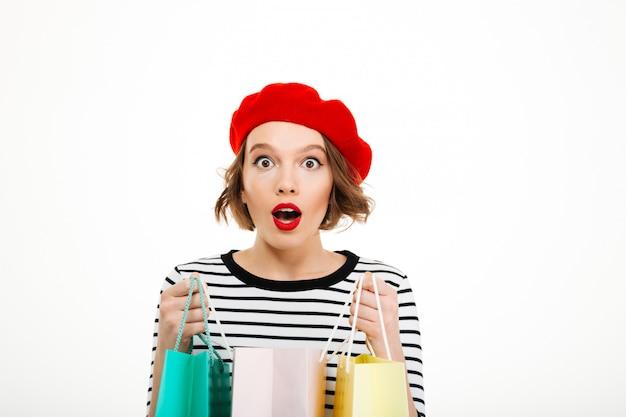 Потрясенная рыжая женщина держит пакеты и смотрит в камеру над серым