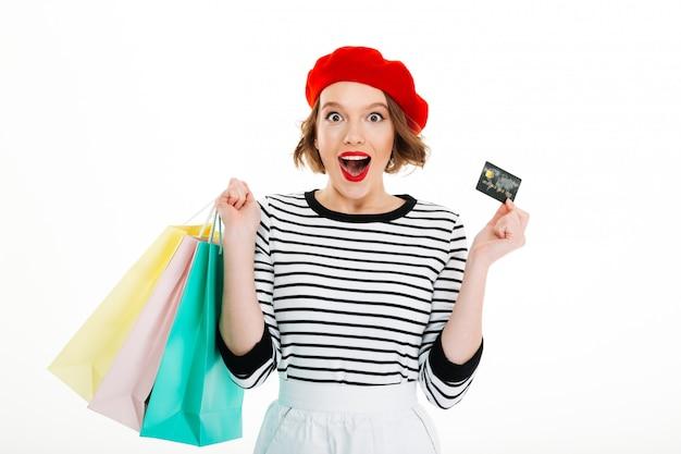 Удивленная рыжая женщина с пакетами держит кредитную карту и смотрит в камеру над серым