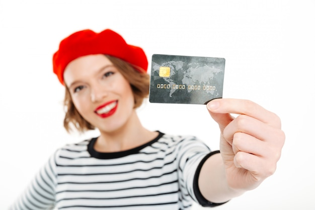 Усмехаясь женщина имбиря показывая кредитную карточку на камере над серым цветом. сосредоточиться на карте