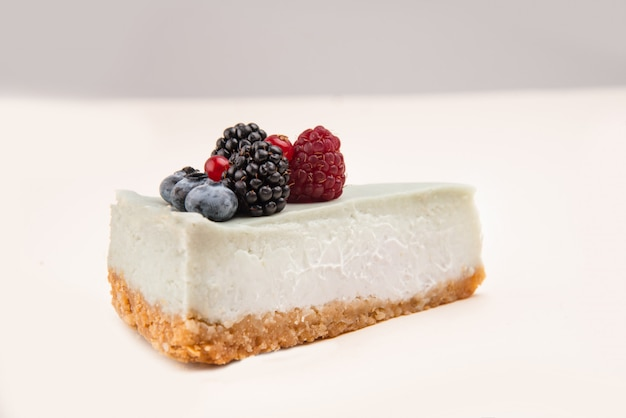 白で分離されたそれの異なる果実と青いチーズケーキの側面図