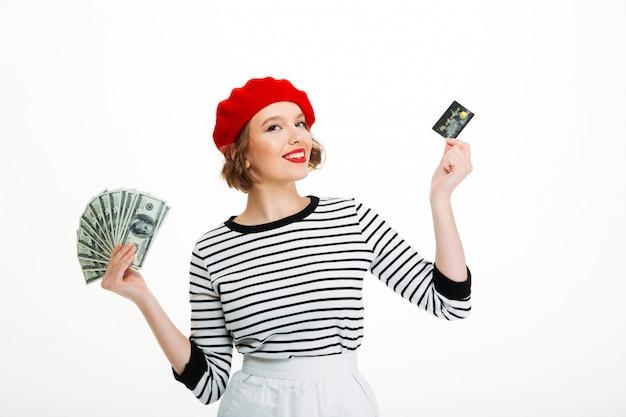 お金のドルとクレジットカードを保持している幸せな若い女性