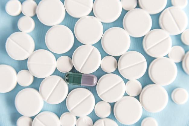 Вид сверху белые таблетки с одной капсулой