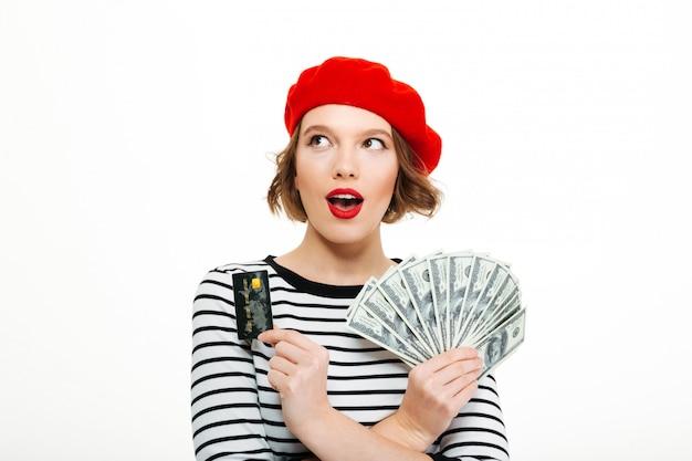 お金のドルとクレジットカードを保持しているショックを受けた若い女性