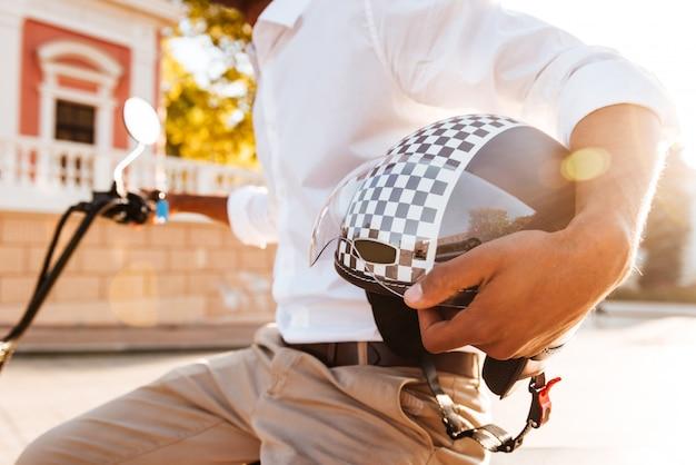 Молодой африканец сидит на современном мотоцикле и держит мотоциклетный шлем на улице