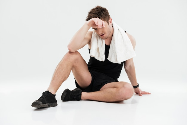 床に座ってタオルで疲れている若いスポーツマン