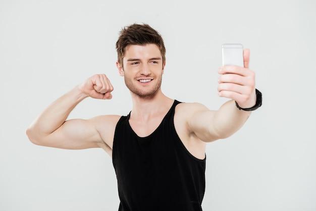 Красивый молодой спортсмен с телефоном делает селфи