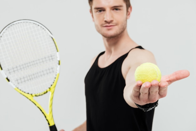 Красивый молодой спортсмен, держа теннисный мяч и ракетку