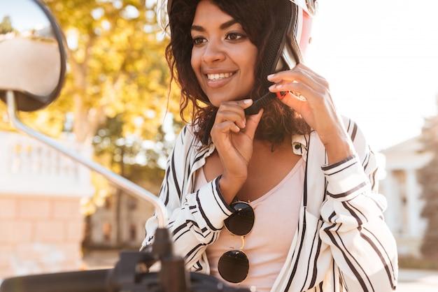 現代のバイクに座っている幸せなアフリカの女性と彼女のモトヘルメットを屋外に固定