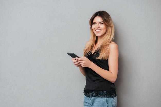 Молодая женщина держит мобильный телефон и смотрит в камеру