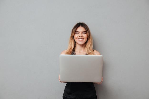 Улыбающиеся женщина, держащая портативный компьютер и глядя на камеру