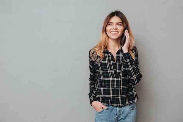 携帯電話で話している幸せな若い女の肖像