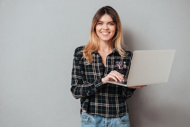 Портрет счастливой жизнерадостной женщины используя портативный компьютер