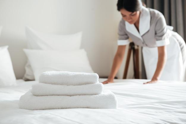 Молодая горничная расставляет подушки на кровати