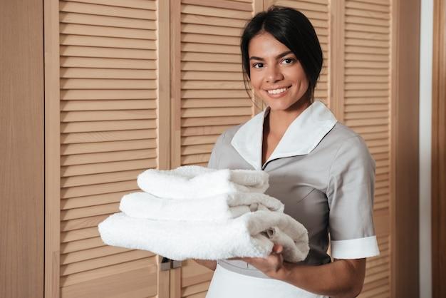 新鮮なきれいな折り畳まれたタオルを保持しているホテルのメイドの肖像画