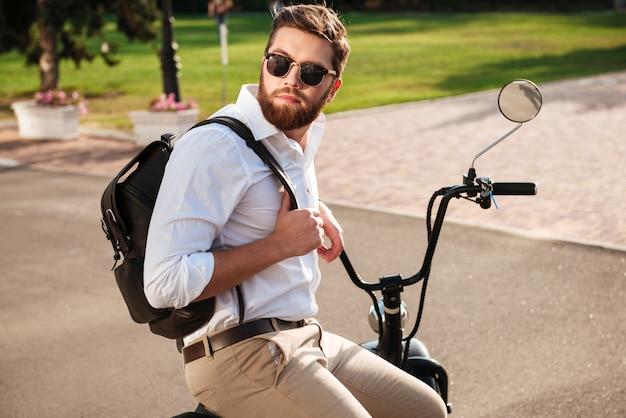 モダンなバイクの屋外に座っているとよそ見のバックパックとサングラスで穏やかなひげを生やした男の側面図