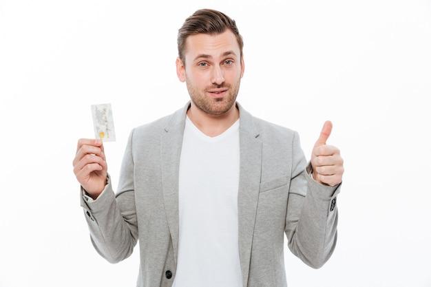クレジットカードを保持している親指を示すハンサムな青年実業家。
