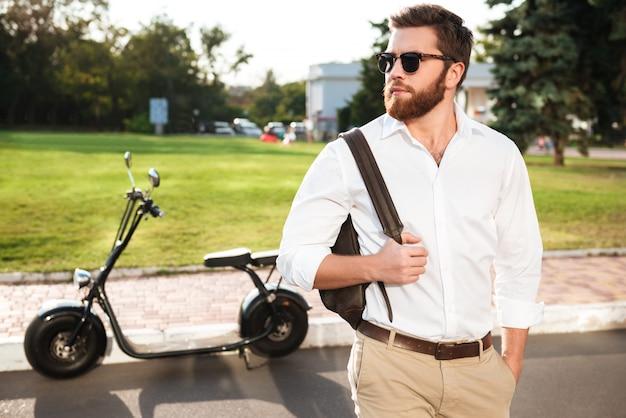 Красивый бородатый мужчина в темных очках позирует на улице с современным мотоциклом на фоне