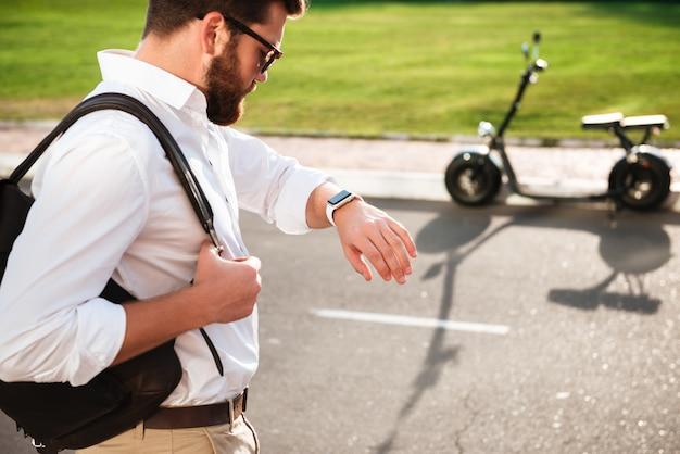 Спокойный бородатый человек в темных очках держит рюкзак и смотрит на наручные часы, позируя на улице с современным мотоциклом на заднем плане