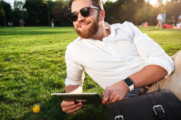 Счастливый бородатый человек в темных очках, лежа на траве на открытом воздухе с планшетного компьютера и глядя в сторону