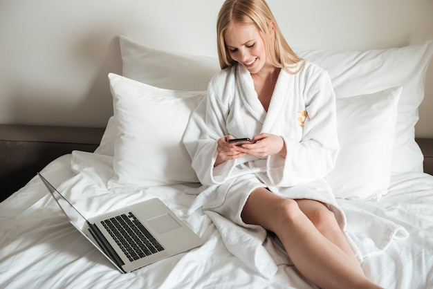 Женщина лежит в постели и разговаривает по мобильному телефону