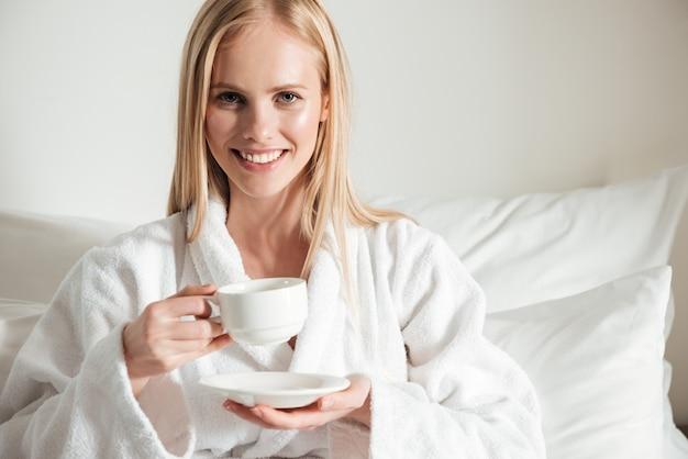 一杯のコーヒーを保持しているバスローブで幸せな笑顔の女性