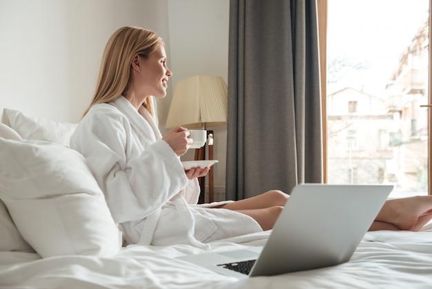 コーヒーを飲みながらバスローブで若いきれいな女性