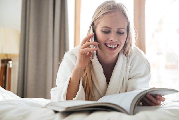 Молодая блондинка читает журнал и разговаривает по телефону