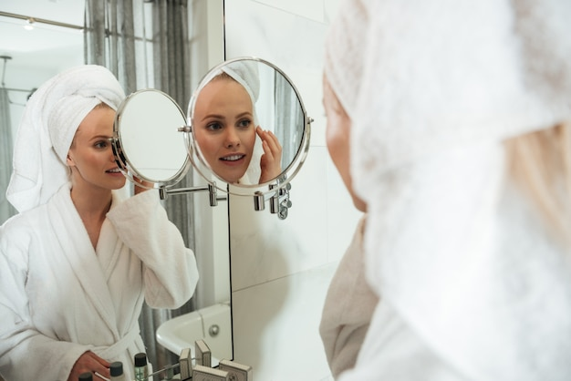 Молодая блондинка смотрит в зеркало, чтобы применить косметику