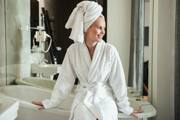 Улыбающаяся женщина смотрит в сторону, сидя в ванной комнате