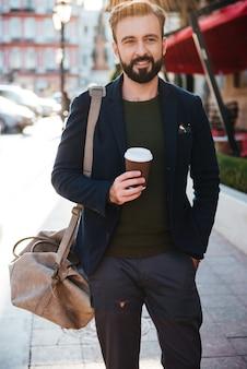 コーヒーを飲みながら笑顔のひげを生やした男の肖像