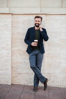 コーヒーカップを保持している笑みを浮かべて男の完全な長さの肖像画