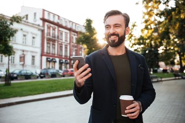 携帯電話を保持している笑顔の若い男の肖像